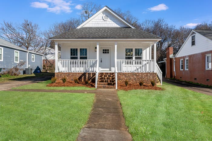 exterior home reno |Real Estate Lingo by popular US house flipping blog, The Inspiring Investment: image of a white house with a covered front porch.