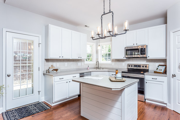 kitchen renovation |Real Estate Lingo by popular US house flipping blog, The Inspiring Investment: image of a kitchen with white cabinets, wood floor, modern chandelier, and island with grey countertop.