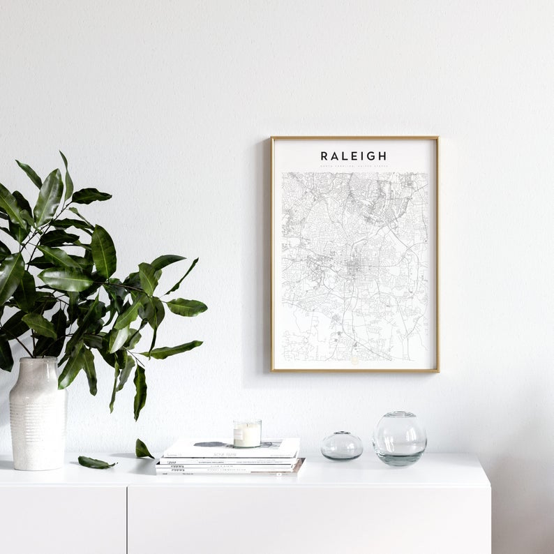 a black and white print of raleigh in a wood frame mounted on a white wall. an example of how this could be used in an office