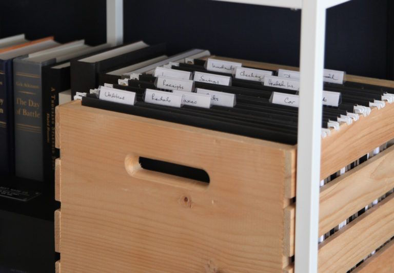 picture of a wooden crate being used to store files in a home office and styled on a shelf with pretty books this design tip also helps you stay organize