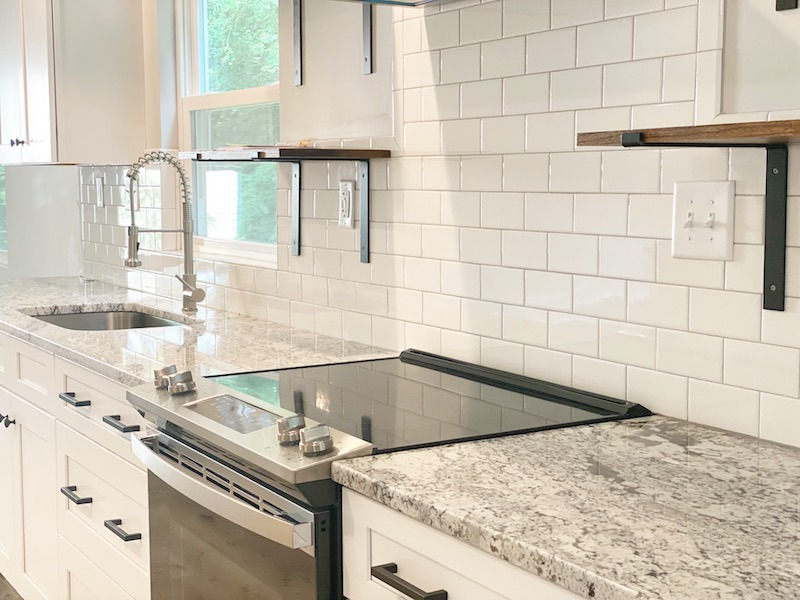 this is a picture of a kitchen in one of our standard flips with floating shelves, subway tile, matte black hardware and a farmhouse lighting package