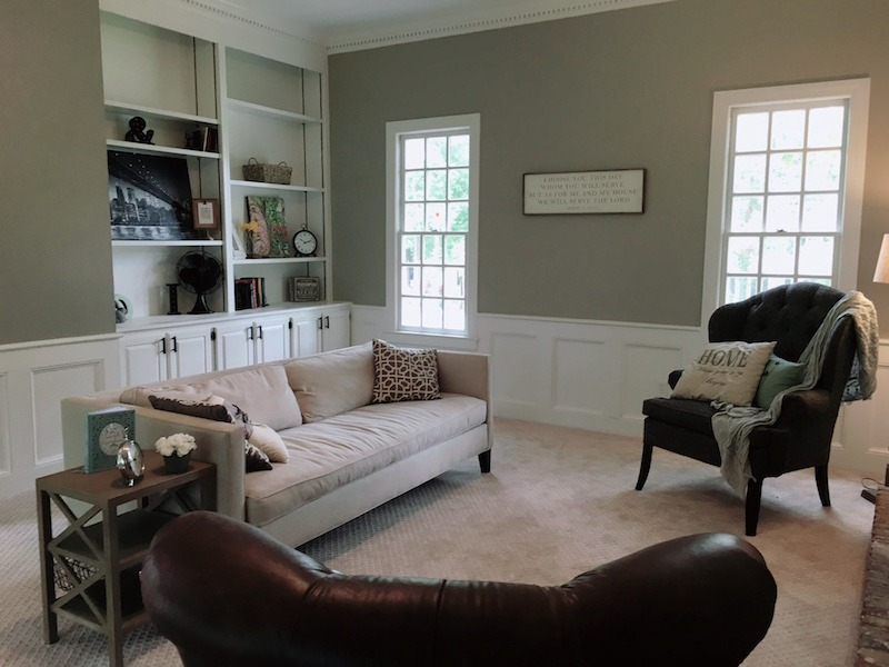 This image is of the same living room above, but after renovation with new carpet, white painted trim and wainscoating. The living room and book built-in bookcase is staged for showings.