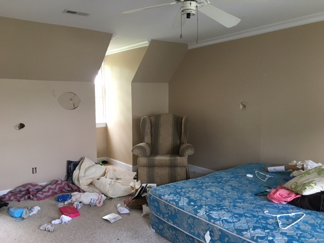 master bedroom before renovation at flip house in raleigh. room is in disprepair with holes in the walls