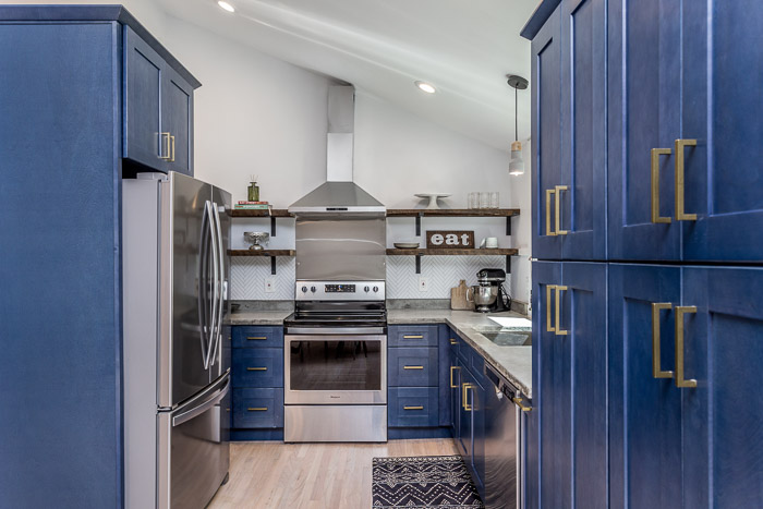 diy kitchen countertops after | DIY Concrete Countertops by popular US DIY blog, The Inspiring Investment: image of a kitchen with light wood floors, blue cabinets, concrete countertop, floating wood shelves, and kitchen appliances.