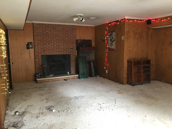 living area of ranch house before   Mid Century Modern Flip by popular US house flipping blog, The Inspiring Investment: image of a mid century modern living room with wood paneling, brick fireplace, and red Christmas lights handing from the ceiling.